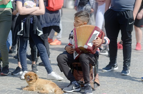 child playing music on a crowded street
